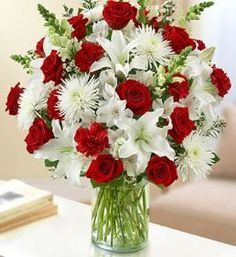 Sincerest Wishes Red and White Arrangement Express a memorable time of days gone past with our lush red and white vase arrangement. Roses, lilies, snapdragons, spider mums, carnations and alstroemeria