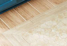 Create the illusion of wood flooring with plank-like porcelain tile. Then create the look of a rug by insetting a small area with a border of rectangular tiles surrounding a hex-and-square mosaic tile center.