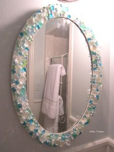 Mirror in small bathroom is a DIY with sea glass, crystals and glass gems.