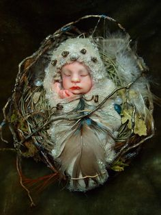 Fairy Nursery  #24    This is an original One-of-a-kind Art Doll Fairy Baby on a nest. The head has been hand-sculpted from polymer clay and painted with Genesis oil paints. The body is wire covered with fibers and decorated with feathers, twigs and a miniature snail shell.  The nest measures 2.5 inches (6,5 cm) in diameter and is hand-made from twigs and dried grass, its decorated with some leaves, feathers and beads.      ✤ Thank you for looking and please convo me with any questions you…
