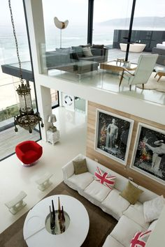 Peering down from the mezzanine to the open plan living area below is a furnished room adorned with modern art and pristine white furniture.