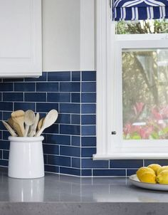 Blue subway tiles with white accessories are perfect in this kitchen