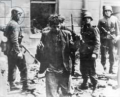 A Jewish insurgent is captured by German soldiers during the Warsaw Ghetto Uprising, 1943 (b/w photo)