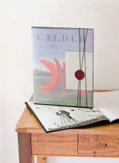 """Guests who stayed at nearby hotels received a book of Calder artwork, vellum-wrapped and wax-sealed. """"We wanted the feeling of a destination,"""" Ashley says of the Hudson Valley locale. """"Sam put a lot of effort into finding the perfect place where our families could stay and make a weekend of it."""" #welcomebags #welcomegift #weddingwelcomegifts #weddingideas 