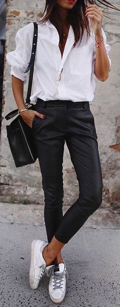 #spring #outfits woman in white button-up shirt, black pants, white low-top sneakers, and black bag standing behind grey wall. Pic by @i__am_fashion