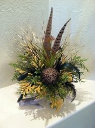 Silk Floral Arrangement made on a naturally shed deer antler with feathers.