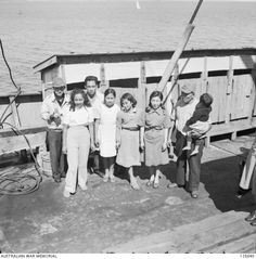 PORT MELBOURNE, VIC. 1946-02-21. A JAPANESE FAMILY ON THE DECK OF THE KOEI (KOEYI) MARU. THE SHIP, A FORMER JAPANESE MINELAYER STILL CREWED BY NAVAL PERSONNEL, ARRIVED TO REPATRIATE 2800 INTERNEES ...