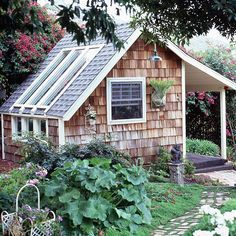 Potting Shed Greenhouse-A charming wood-shingled backyard structure is part greenhouse and part garden shed. South-facing windows bathe the interior of the structure in light for potting projects (and plant propagation). An open front porch makes the shed look like a tiny house. The doors and windows allow air to flow inside. Exterior landscaping helps the structure fit naturally into the garden.