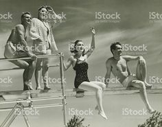 Two couples on springboard, (B&W), low angle view royalty-free stock photo