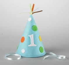 "For your special birthday child, try this cone style felt fabric party hat with colorful matching ribbon straps. Each hat stands 7"" tall, matches the Sweet At One Boy pattern, and features sewn-on colored felt polka dots and a white felt number ""1"". 1 per package."