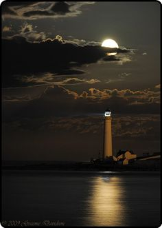 lighthouse with moon, clouds and sea