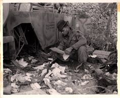 "34th Division Corporal Joseph P. Belnius inspects some paperwork found in an upturned German staff car somewhere near San Vittoro Italy, 9 January 1944. Scanned from an original 8"" X 10"""