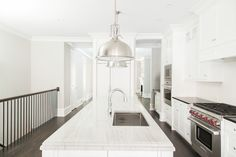 Beautiful kitchen features white shaker cabinets paired with honed black countertops and subway tiled backsplash flanking concealed range hood hidden within faux cabinets over Wolf Range beside built-in microwave stacked over oven.