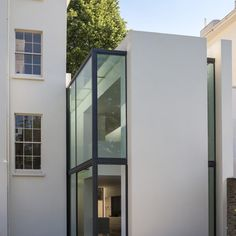 Narrow slices of glazing break up the plain white facade of this London house extension, helping to visually separate it from the original house.
