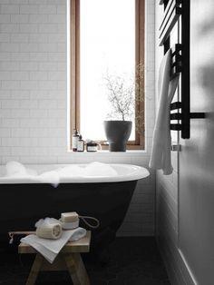 Black claw foot tub. Black and White bathroom design idea with mid grey walls. Minimal and bright.