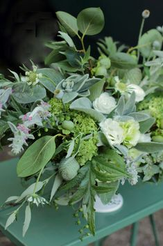 Centerpiece. Green & white bouquet from the yard. Lamb's Ear. Green pine cone. Baby Persimmon. Tiny grape tomatoes. Hydrangea. White Roses.