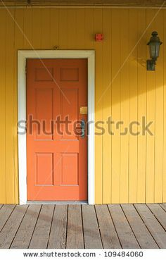 pastel yellow house with white borders and peach front door. so