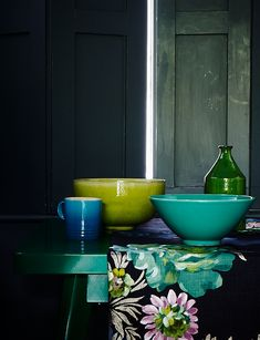 Interior still life styled by Mary Norden. Lime and aqua and green ceramics sit against an inky dark interior