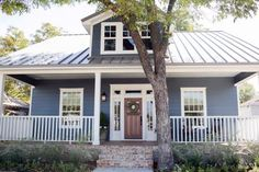 To transform the exterior, the old stucco was removed and the front porch opened up and enhanced with new railing, trim and columns. A new front door in natural wood finish was added as well as a new skirt and stairs in antique brick. A new metal roof was added as well as fresh landscaping.