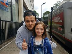 Harry with a fan in London. // the snap f*cking back, that smile, he's with a kid; someone hold me pls