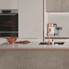 Create an eye-catching look in your home by pairing concrete effect kitchen units with a copper trim. Enhance the warm qualities of this colour palette with White Quartz worktops. Click the link in our bio to find out more.