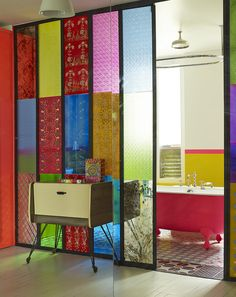 Manish Arora Paris Apartment - A stained-glass sliding door separating the kitchen and bathroom of a Paris apartment
