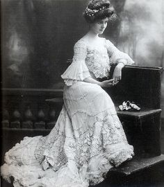 Actress Carroll McComas poses for the camera in 1905. Her clothes are typical of those of the elegant woman of the time, with an abundance of lace and frills and sweeping skirt. The waist was pulled in by corsets, and the bosom flung forward, but dress bodices fell loosely, billowing slightly over the waistband at the front. This would have been an evening dress, as high-collared dresses were always worn for day