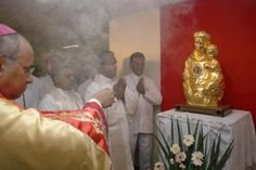 Catholic priest burning incense in front of gold idol with a tongue place where people normally find the heart.
