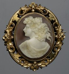 A shell cameo brooch  The first depicting the profile of a Bacchante, with closed back setting within a pierced foliate border, Victorian or Victorian style