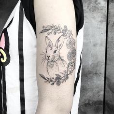 Tatuagem feita por Jay K de Frankfurt, Alemanha.    Coelho com meia lua formada por flores delicadas no braço.
