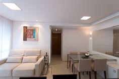 Mesa de jantar em aço inox e vidro, projetada sob medida é fixada na parede. Sob a mesa, armário com portas de correr. O espelho em tiras amplia a pequena sala.