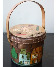 Vintage 60s 70s Small Round Caro-Nan Basket Purse Handbag This super cute vintage purse is by Caro-Nan has a whimsical holiday travel theme. It has a 1969 penny on the top, along with several decoupage doo-dads. The basket body is painted with a little street scene, and has a topstitched leather band around the top. The lining is golden yellow with little flowers and diagonal quilting.