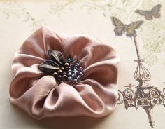 I think you could use silky fabric and a loose stitch to create yo yos to make these type of flower accessories.  You can embellish the center or attach a broach if you want to make it interchangeable.