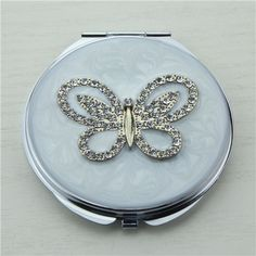 Crystals butterfly compact mirror It is covered with white enamel glaze and mounted with bling-bling crystals and elegant pearls.