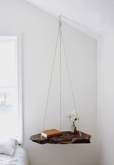 Try this simple idea to make your own hanging bedside table from a piece of natural wood and rope. Find home styling ideas at Decorator's Notebook.