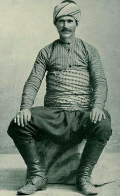 A Turkish villager in his best outfit.  Not wealthy, but not poor either (note the leather boots). The primary purpose of the large men's  'kuşak' (waist band) is here obvious: to support the back during demanding daily activities.  Late-Ottoman, end of 19th century.