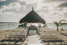 Cerimônia de casamento na praia com cadeiras brancas e altar em um gazebo de sapê. Foto: Renata Xavier