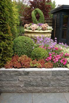 Natuursteen is een prachtig en karaktervol materiaal om delen van uw tuin mee te bestraten. De tegels kunt u combineren met bijbehorende muurelementen en stapelblokken. Het wordt een harmonieus geheel als u de bestrating door laat lopen in een bloembak, een rand of een trapje.