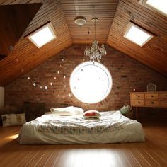 Who needs a bed in this light-filled architectural interesting attic conversion. The opposing parallel lines of the floor and roof is perfectly broken up with the exposed brick. Also the play on opposing shapes in the window and skylights create additional interest in the space
