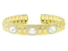 From the Classic 18K Collection, the Quilted Oval Station Diamond Cuff features oval white topaz surrounded by pave round diamonds set in quilted 18K yellow gold.
