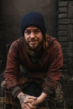 Portrait of young homeless man looking at camera with hopeful eyes by Rob and Julia Campbell for Stocksy United