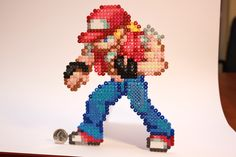 Terry Bogard is pretty cool. I have a friend that would love this This version was designed by the Card Saga War's artist and Perler Beads CSW Terry Bogard Stitch Games, Cool Pixel Art, Peler Beads, Minecraft Pixel Art, King Of Fighters, Perler Patterns, Bead Art, Beading Patterns, Decoration
