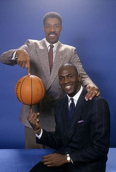 Michael Jordan and Julius Erving pose with a spinning basketball for a photo session.