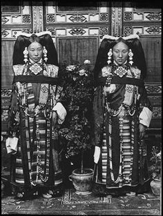 Photographer: Rabden Lepcha?, Collection: Sir Charles Bell, Date of Photo: 1920-1921. The Prime Minister Lonchen Shokhang's daughter on the right, with Captain Tsoko's wife on the left. The two women are standing in a lavishly furnished room with carved wall panels. The women are wearing all the accoutrements of high status, such as amulets, beads and other jewellery, rich textiles, and elaborate Lhasa-style head dresses.