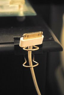 Just stick the end of your charger into one of these do-dads and clip it to your desk. If the end of your charger is to small and slips though you could always tie it around the clip (make sure you tie it loosely so you don't damage the cord)