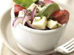 A Greek inspired vegetable salad with tomatoes, cucumbers, red onion, feta and mozzarella cheese with a lemon flavored vinaigrette.
