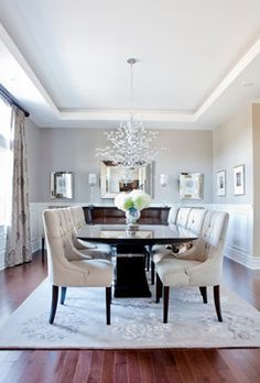 Rebecca Mitchell Interiors & Boutique designed this transitional dining room with traditional wainscoting, brown pedestal table, and stunning chandelier. The Surya Tamira rug adds a little metallic touch. (TAM-1041)