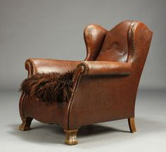 Armchair in chesterfield style upholstered in brown studded patinated leather.