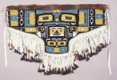 """2004-2/103 Apron Tsimshian MAKER William White MATERIALS   Wool, Fur, Deer Hoof, Copper Ore, Leather, Wood, Sinew, Cloth, Chilkat Weaving,   'Spirit of the Ancestors' - This apron is the only contemporary """"Chilkat"""" style weaving in the Burke's collection, and was woven by the only male Native weaver known to use this technique. Many believe that Tsimshian women originated this complex technique of weaving in the late 18th or early 19th centuries. depicts a Raven with wings outstretched."""