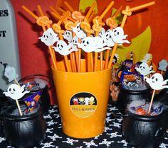 Mesa decorada com caldeirões pretos cheios de doces e canudinhos com imagens de fantasmas. #Halloween #Trickortreat